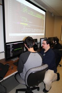 Computer graphics and programming instructor working with a student